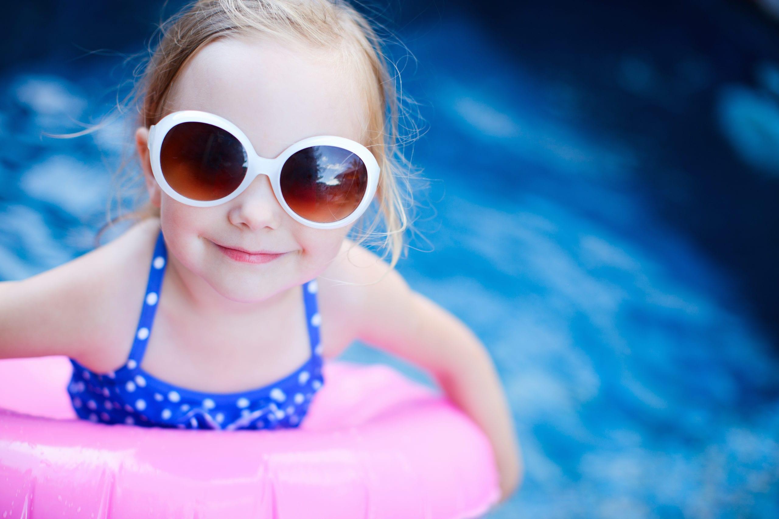 little girl wearing sunglasses in a pool